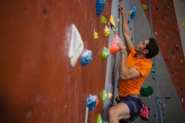 Man wall climbing in gym